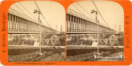 Stereoview showing woman walking by side of the railway suspension bridge at Niagara Falls